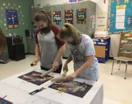 Two students paint